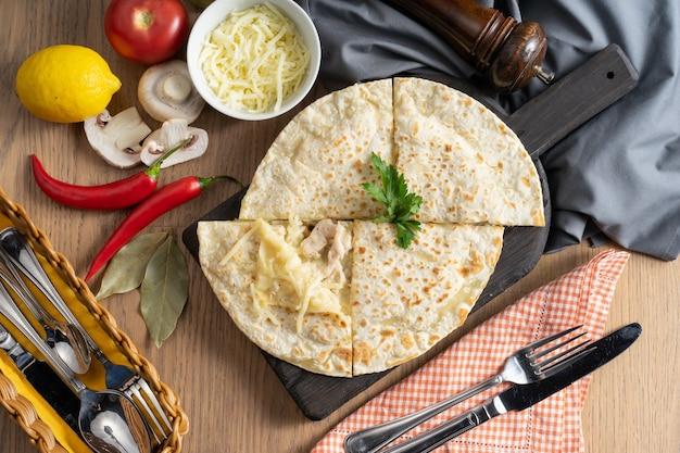 Tortilla z mozzarellą i kurczakiem na drewnianej desce do krojenia