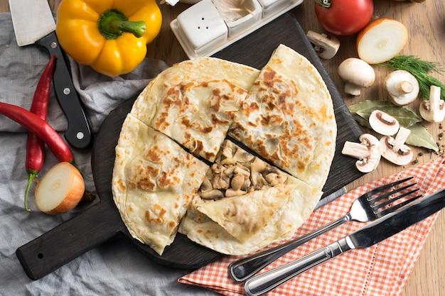Tortilla z pieczarkami i cebulą na drewnianej desce do krojenia