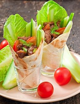 Tortilla zawija się w mięso i świeże warzywa