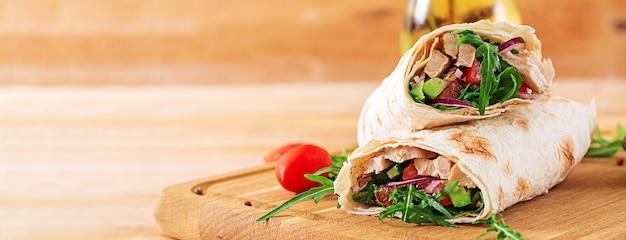 Tortillas zawija z kurczakiem i warzywami na drewnianym tle.