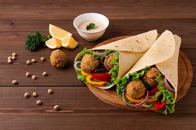 Tortille owinięte kulkami falafel i świeżymi warzywami wegetariańskimi na drewnianym tle