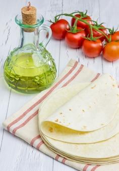 Tortille z mąki razowej z pomidorami i oliwą z oliwek na tle