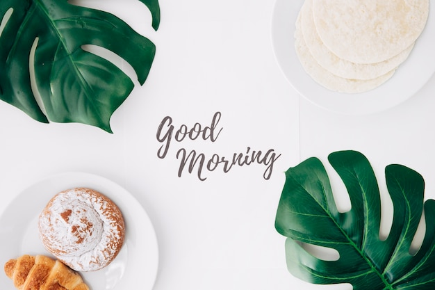 Tortille ze świeżą mąką; pieczona bułka; śniadanie croissant z dzień dobry tekst na papierze i zielonym potworem pozostawia na białym tle