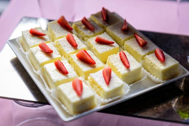 Torty biszkoptowe z kremowym kremem ozdobione świeżymi truskawkami