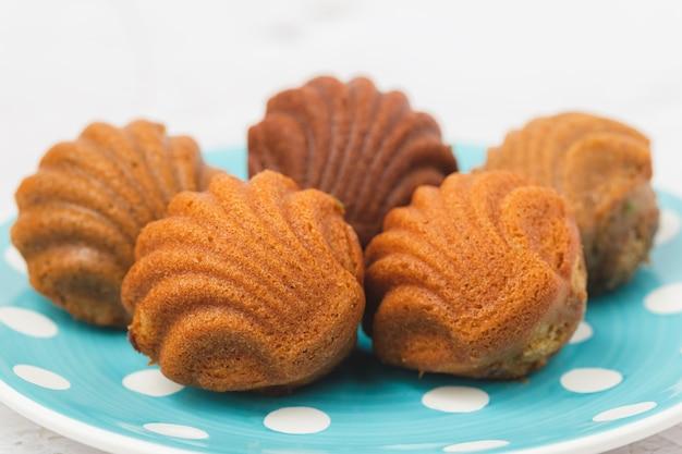 Torty madeleine o charakterystycznym kształcie muszli na białym tle do koncepcji piekarni, jedzenia i jedzenia