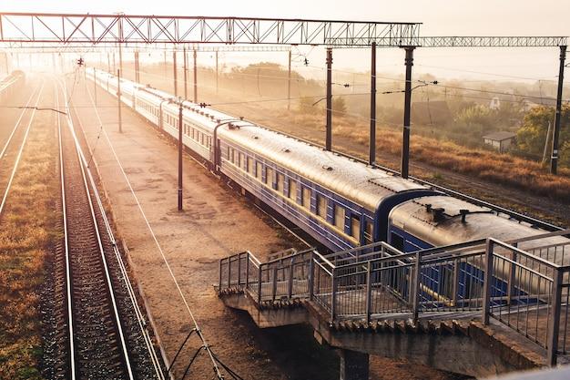 Tory kolejowe z pociągami pasażerskimi pięknie oświetlone zachodzącym słońcem