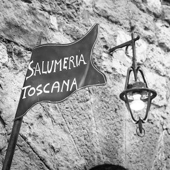 Toskania, włochy. tradycyjny znak uliczny rzeźni na starym murze