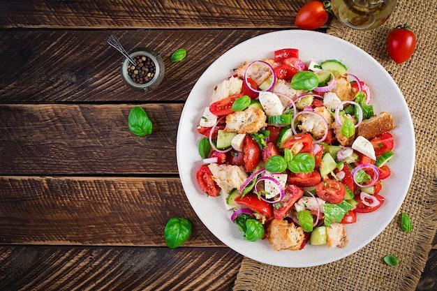 Toskańska panzanella, tradycyjna włoska sałatka z pomidorami i chlebem na drewniane tła. wegetariańska sałatka z panzanelli. zdrowa żywność śródziemnomorska. widok z góry, układ płaski