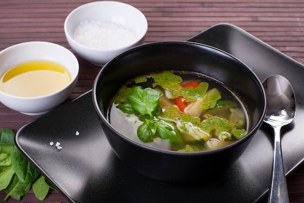 Toskańska zupa jarzynowa z pesto bazyliowym na czarnym talerzu