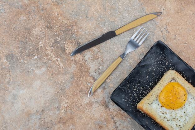 Tost jajeczny z przyprawami na czarnym talerzu ze sztućcami