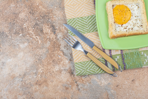 Tost jajeczny z przyprawami na zielonym talerzu ze sztućcami i obrusem