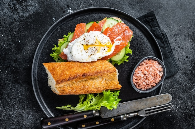 Tost kanapkowy z jajkiem po benedyktyńsku, wędzonym łososiem i awokado na chlebie. czarne tło. widok z góry.