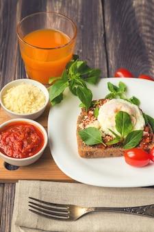 Tost śniadaniowy z jajkiem w koszulce, sosem pomidorowym, bazylią i parmezanem na rustykalnej drewnianej powierzchni