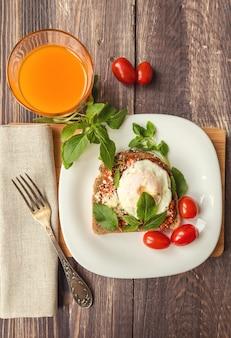 Tost śniadaniowy z jajkiem w koszulce w sosie pomidorowym z bazylią i parmezanem na drewnianym tle