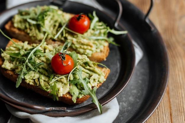 Tost z awokado, rukolą i pomidorkami koktajlowymi podany na żelaznym talerzu.