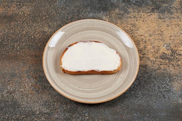 Tost z kwaśną śmietaną na talerzu ceramicznym.