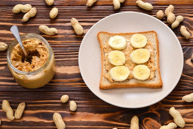 Tost z masłem orzechowym z plastrami banana na drewnianym tle