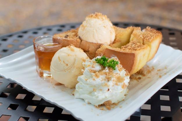 Tost z miodem na stole, przystawka to lody, miód, bita śmietana i posypane pokruszonymi orzechami.