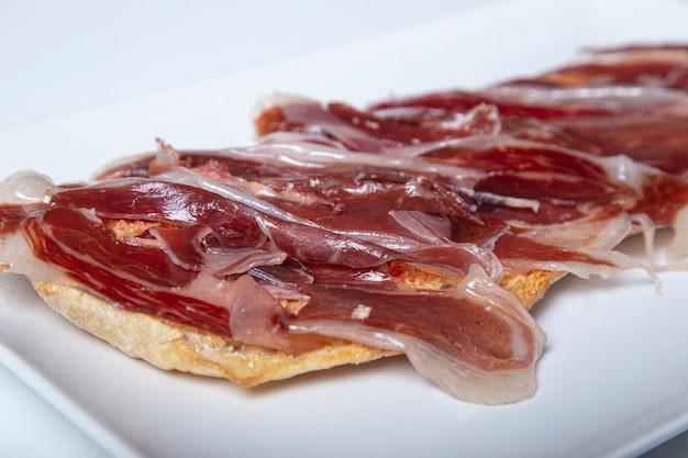 Tost z szynką iberyjską. typowe hiszpańskie jedzenie. pojedyncze zdjęcie. selektywne ustawianie ostrości.
