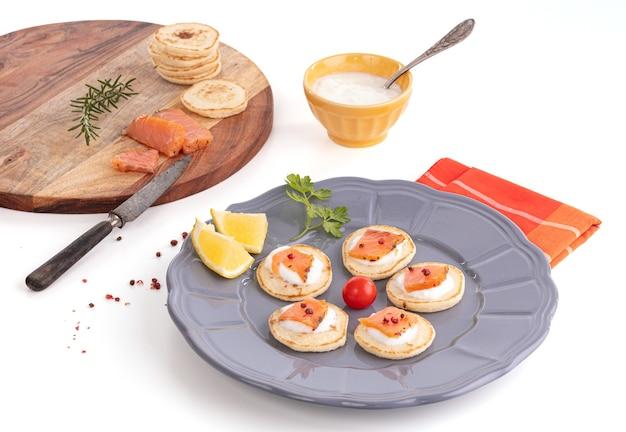 Tost z wędzonego łososia w talerzu ze świeżą śmietaną na białym tle