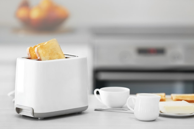 Toster z naczyniami na lekkim stole kuchennym, z bliska
