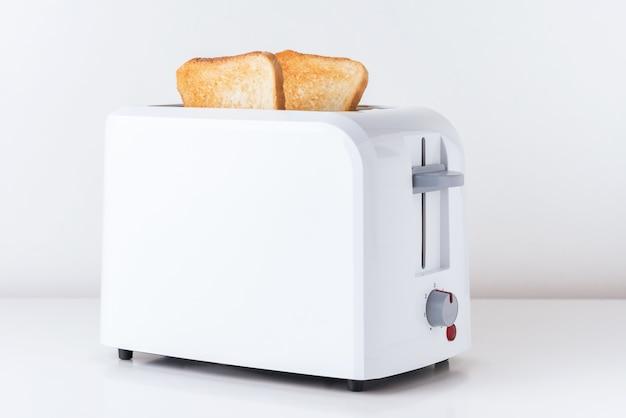 Toster z pieczonym chlebem tostowym na białym tle