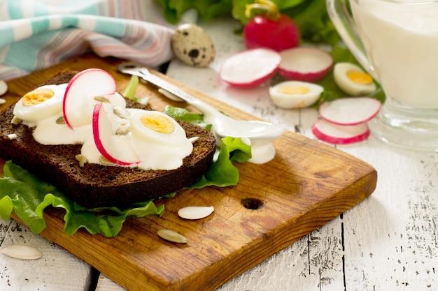 Tostowa kanapka z jajkiem, rzodkiewką, pestkami dyni i kwaśną śmietaną, selektywne focus.