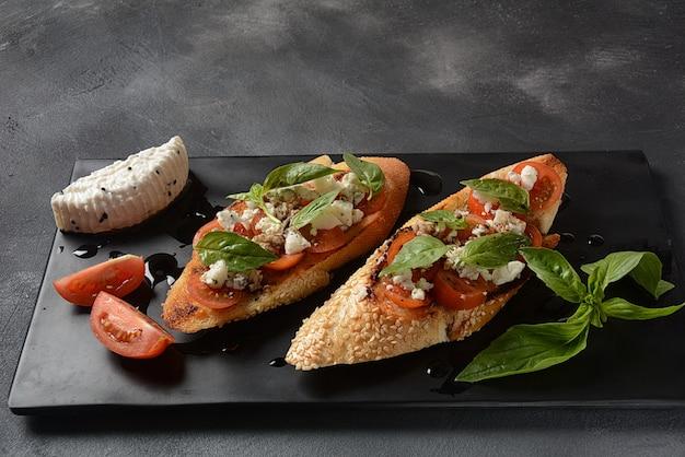 Tosty caprese bruschetta z pomidorkami koktajlowymi, mozzarellą.