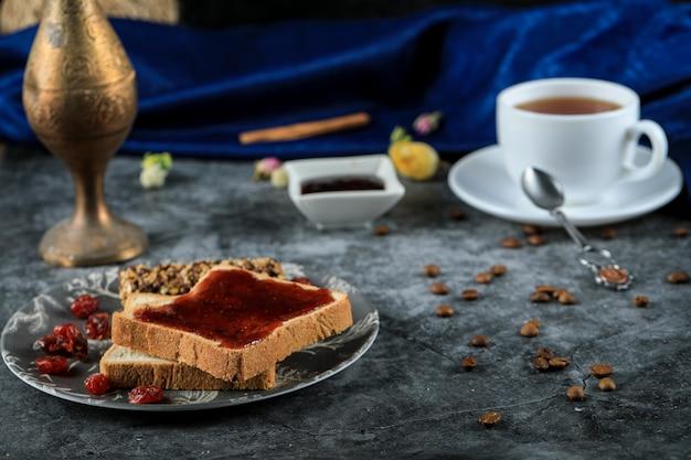 Tosty chlebowe z konfiturą jagodową i szklanką herbaty