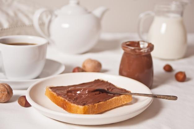 Tosty chlebowe z masłem czekoladowym, słoik kremu czekoladowego, kubek herbaty, słoik mleka, czajniczek na białym.