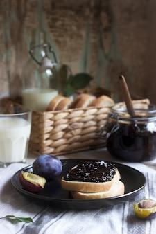 Tosty chlebowe z powidłami śliwkowymi, podawane z mlekiem i śliwkami. styl rustykalny.