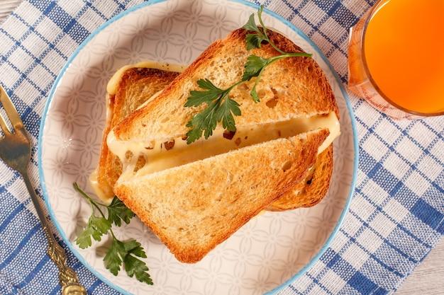 Tosty kromki chleba z serem i zieloną pietruszką na białym talerzu, szklanka soku pomarańczowego z niebieską serwetką kuchenną. dobre jedzenie na śniadanie. widok z góry