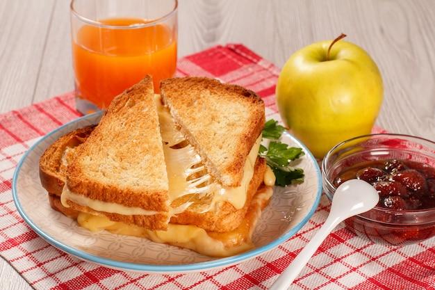 Tosty kromki chleba z serem i zieloną pietruszką na białym talerzu, szklanym soku pomarańczowym og, jabłku, łyżce i szklanej misce z dżemem truskawkowym z czerwoną serwetką kuchenną. jedzenie na śniadanie?