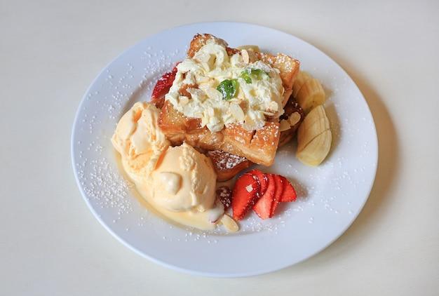 Tosty miodowe podawane z bananem owocowym, truskawką i lodami na białym talerzu.