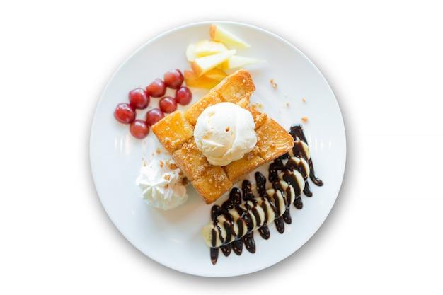 Tosty miodowe z lodami waniliowymi, bitą śmietaną i syropem czekoladowym na białym tle
