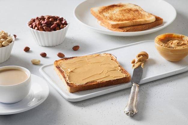 Tosty na śniadanie z pastą orzechową na białym stole.