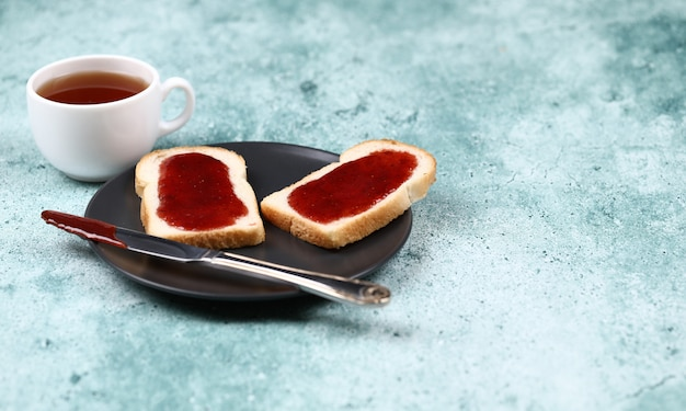 Tosty śniadaniowe z dżemem truskawkowym w czarnym talerzu i filiżance herbaty.