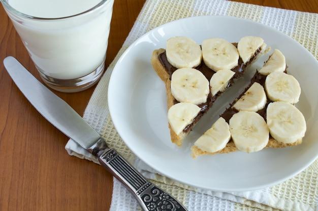 Tosty w plasterkach z kremem czekoladowym i bananem na białym talerzu