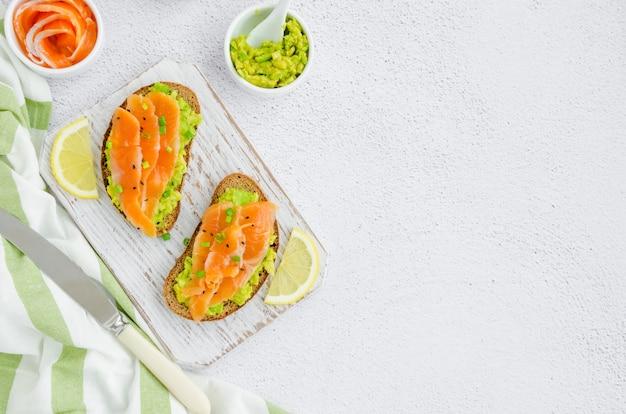 Tosty z awokado. grzanki z chleba żytniego, awokado, wędzonego łososia, zielonej cebuli i sezamu. zdrowe śniadanie lub obiad. orientacja pozioma. widok z góry. skopiuj miejsce.