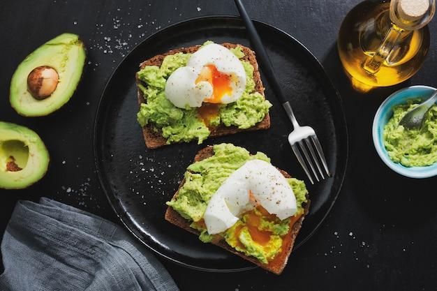 Tosty z awokado i jajkami podawane na talerzu. zbliżenie.