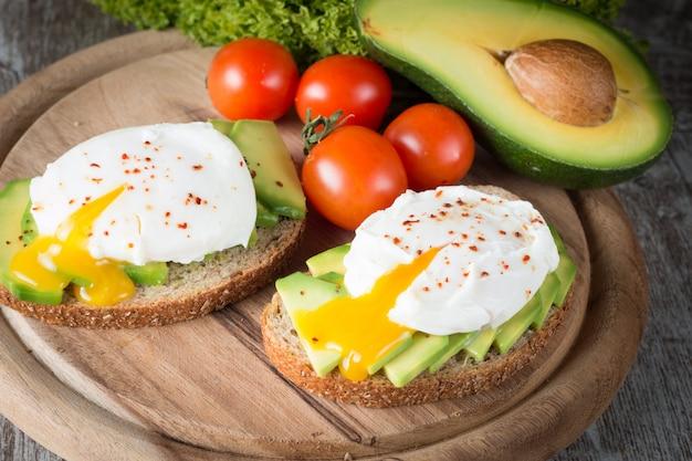 Tosty z awokado, pomidorki koktajlowe i jajka w koszulkach na drewnianym. śniadanie z potrawami wegetariańskimi, zdrową dietą.