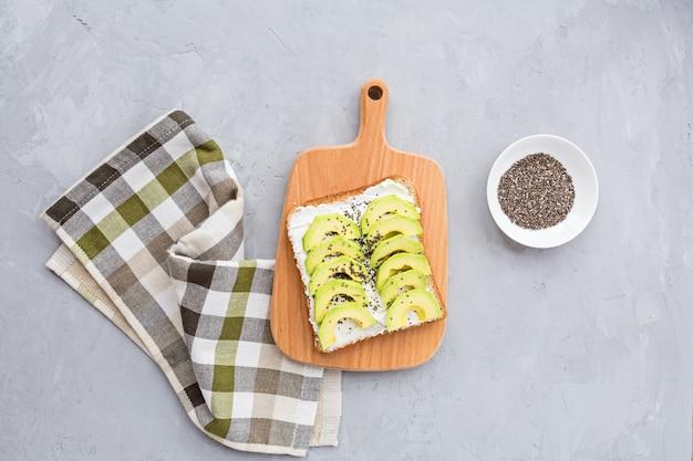 Tosty z awokado z nasionami chia i twarogiem na drewnianym stole