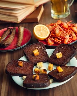 Tosty z brązowego chleba obok smażonych krewetek i cytryny