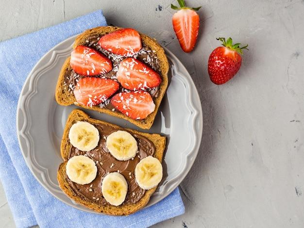 Tosty z czekoladą i owocami na szarym talerzu. truskawki i banany na kamiennym stole w kuchni