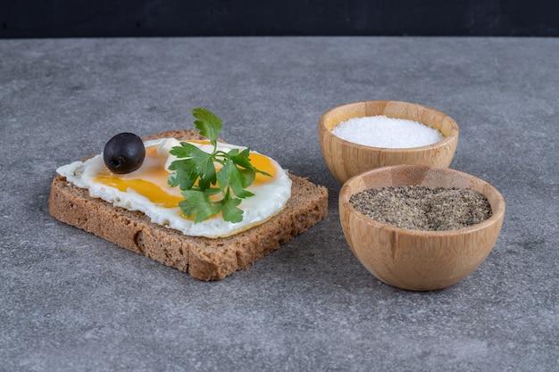 Tosty z drewnianymi miseczkami soli i pieprzu. wysokiej jakości zdjęcie