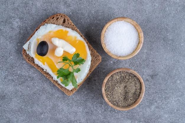Tosty z drewnianymi miseczkami z solą i pieprzem