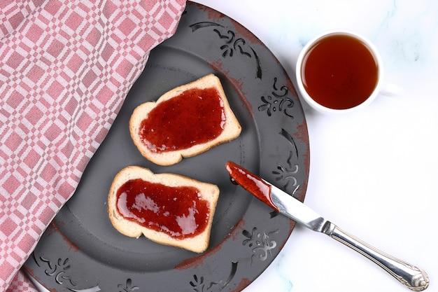 Tosty z dżemem truskawkowym i filiżanką herbaty