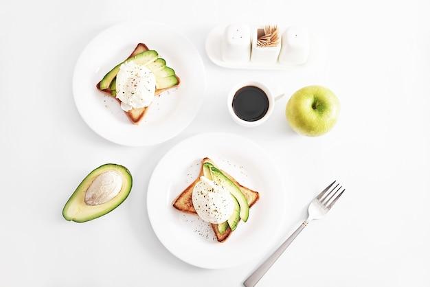 Tosty z jajkiem w koszulce i awokado. zdrowe śniadanie i jedzenie. przytulny poranek. odżywianie dla kobiet w ciąży. dieta dla kobiet. śniadanie w pokoju hotelowym lub łóżku. kanapka z jajecznicą.