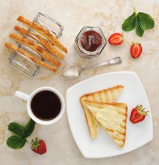 Tosty z masłem i dżemem na talerzu i filiżance herbaty