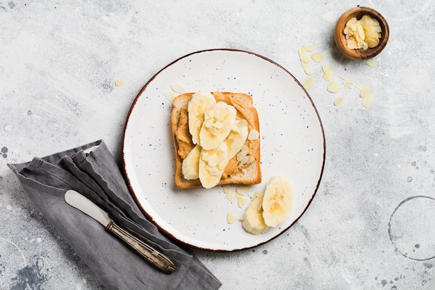Tosty z masłem orzechowym, plasterkami banana, miodem i płatkami migdałów na starym szarym betonie